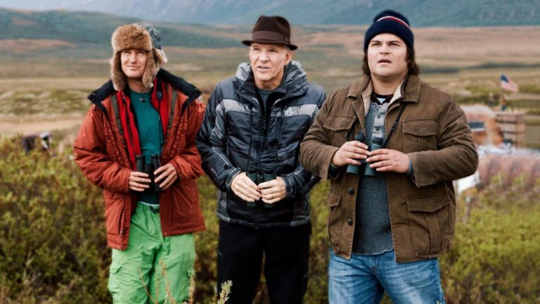 Still Image of The Big Year (2011). Owen Wilson, Steve Martin, and Jack Black stand in a field holding binoculars, preparing themselves to spot birds.